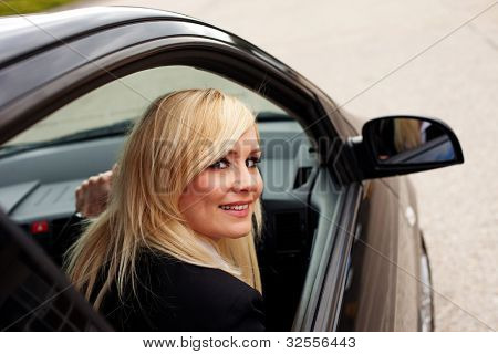 Attractive blonde female driver behind the wheel of a right hand drive vehicle looking out of her window with a smile