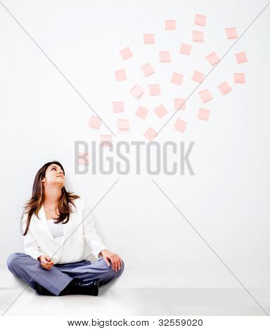 Thoughtful business woman with a bubble of post its - isolated over white