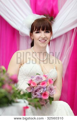 happy bride wearing white dress holds beautiful bouquet of roses