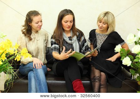 three young women sit on black leather couch and browse journal