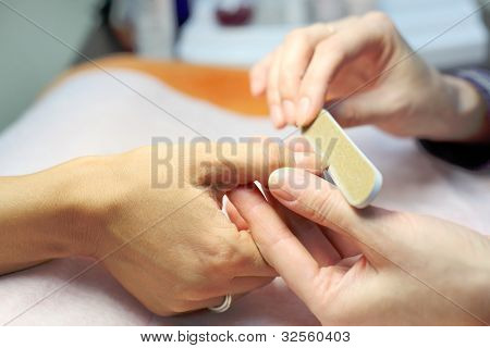 Female hands make manicure by nailfile for woman in beauty salon
