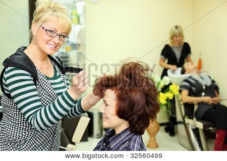 Smiling hairdresser makes hair styling for woman by rake-comb and looks at camera in beauty salon; focus on barber; other barber washes second client head