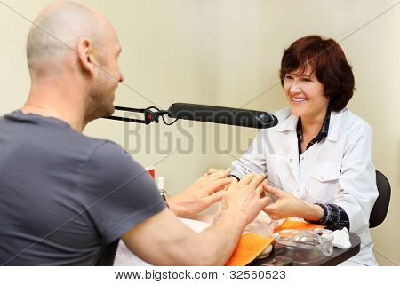 Smiling woman dressed in white coat manicure man in beauty salon
