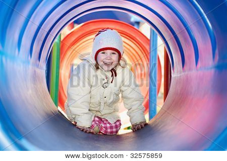 little happy baby girl laughing in plastic tube at children playground at spring outdoors