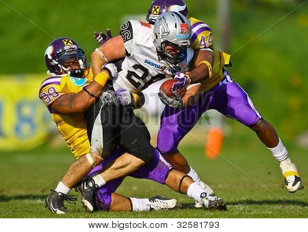 VIENNA, AUSTRIA - APRIL 17 RB Florian Grein (#26 Raiders) is tackled by LB Christopher James (#44 Vikings) and DL Brandon Collier (#99 Vikings) on April 17, 2011 in Vienna, Austria.