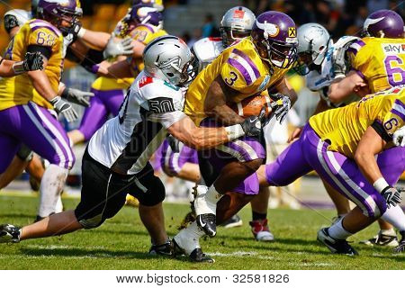 VIENNA, AUSTRIA - APRIL 17 RB Tony Hunt (#3 Vikings) is tackled by DL Mario Rinner (#50 Raiders) on April 17, 2011 in Vienna, Austria. The Vienna Vikings beat the Swarco Raiders 28:24.