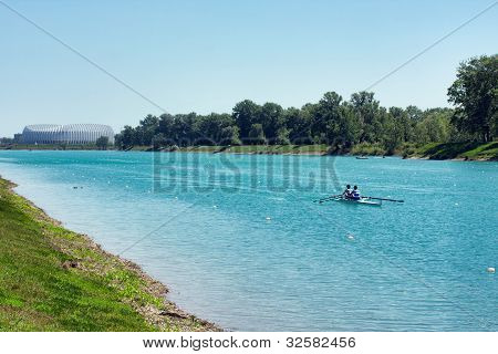 Two Young Men Rowing On Lake Jarun, Arena Zagreb In Back, Croatia