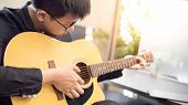 Young Asian Man Guitarist Playing Music With Acoustic Guitar At Home. String Musical Instrument For  poster