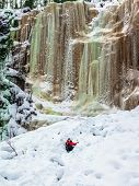 Happy hiker goes down in deep snow. The frozen waterfall picturesquely fall off a steep cliff.  Lapl poster