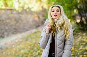 Oversized Jacket Trend. How To Rock Puffer Jacket Like Star. Girl Fashionable Blonde Walk In Autumn  poster