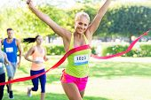 fitness, sport and success concept - happy woman winning race and coming first to finish red ribbon  poster
