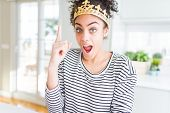 Young african american girl wearing golden queen crown on head pointing finger up with successful id poster