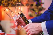 Male Hands Opening Champagne Bottle On Christmas Decorations Background. Open Champagne And Celebrat poster
