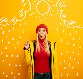 Girl Indicates The Sun Between The Clouds Above. Amazed And Shocked Expression. Yellow Background poster