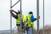 Professional Scaffolders Erecting Scaffolding On A Building In The Uk poster