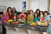 stock photo of niece  - Large Hispanic family in kitchen with food - JPG