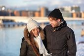 Happy winter friends couple laughing together walking in city outdoors wearing cold weather accessor poster