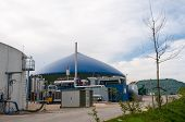 stock photo of biogas  - Different fermenters of a biogas plant in front of a cloudy blue sky - JPG
