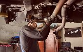Side Cropped View Of Auto Repairman Bending Under Bottom Of Car While Fixing Exhaust System Of Car.  poster