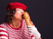 Portrait Of A French Comic Woman In Red Hat And Striped Red-white Shirt Holding And Kissing Baguette poster