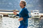 Active Senior Man Jogging On The Pier On A Sunny Day poster