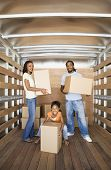 stock photo of nuclear family  - African family holding boxes in moving truck - JPG