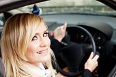 Attractive blonde woman driver seated behind the wheel of a right hand drive vehicle looking out of