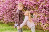 Love Is In The Air. Couple Adorable Lovely Kids Walk Sakura Garden. Tender Love Feelings. Little Gir poster