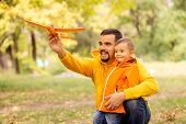Father And Little Son Play Together In Autumn Park Or Forest. Dad Is Embracing Child And Launching O poster
