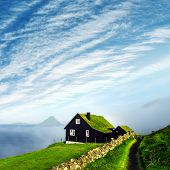 Foggy morning view of a house with typical turf-top grass roof and blue cloudy sky in the Velbastadu poster