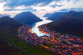 Fantastic aerial evening cityscape of Klaksvik town with glowing streets and fjord, Bordoy island, F poster