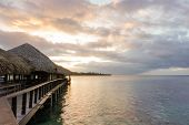 A Wooden Walkway With Thatched Roof Bungalows Leads Out Into The Lagoon On The Island Of Moorea In F poster