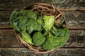 Broccoli Cabbage In A Wicker Basket. A Lot Of Broccoli In A Wicker Box On A Brown Background. Vintag poster