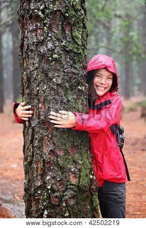 Happy beautiful young woman in an anorak standing hugging a tree in misty woodland as she strives to protect the environment and promote sustainability