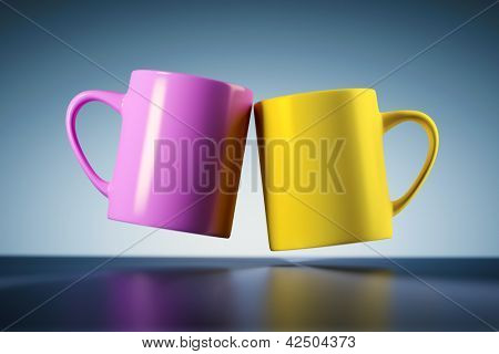 An image of two weightless coffee mugs