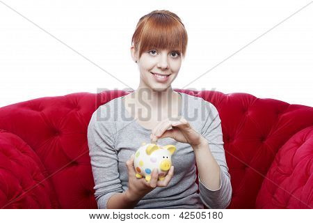 Young Beautiful Red Haired Girl Put Coin In Piggybank On Red Sofa In Front Of White Background