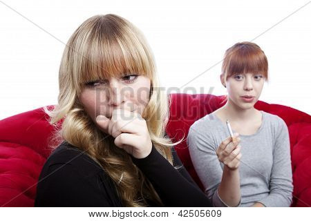 Young Beautiful Blond And Red Haired Girls On Red Sofa In Front