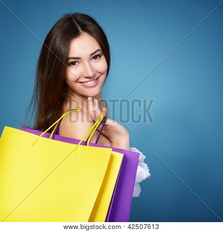 beautiful shopping girl with vivid colored sale bags over blue background