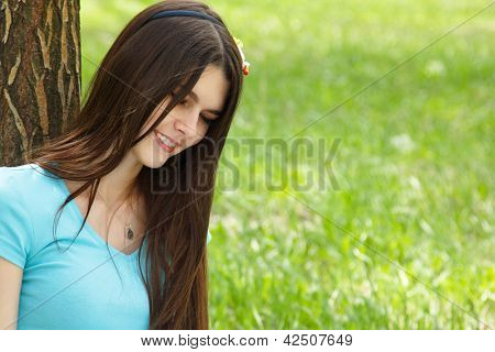 spring outdoor portrait of young cheerful attractive woman with long brown hair sitting near tree on green grass