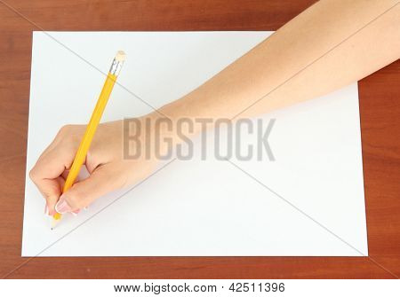 Hand with pencil on white paper, on wooden background