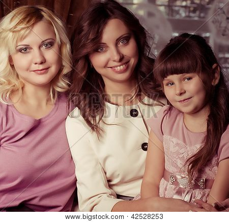 Happy family, young beautiful mother, aunt and her little daughter embracing