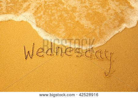 Wednesday - written in sand on beach texture - soft wave of the sea (days week series)