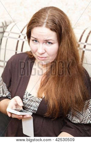 Portrait Of Caucasian Unhappy Young Woman With Cellphone In Domestic Room