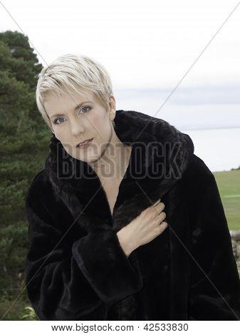 Naked beautiful blond wearing a fur coat