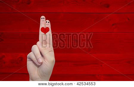 Two hand fingers with a heart painted over a red wood pattern vintage  background