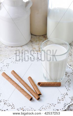 High angle view of a glass of milk and wafer cookies on a kitchen counter. Vertical format.