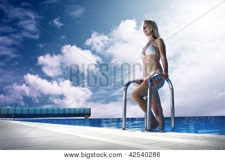 Beautiful happiness girl in white bikini stay near the waterpool