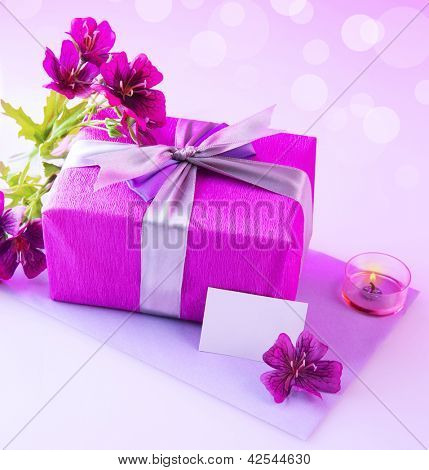 Photo of pink giftbox with silk bow, fresh purple flowers, candle and blank postcard isolated on blur background, festive still life, happy mothers day, romantic holiday, love and romance concept