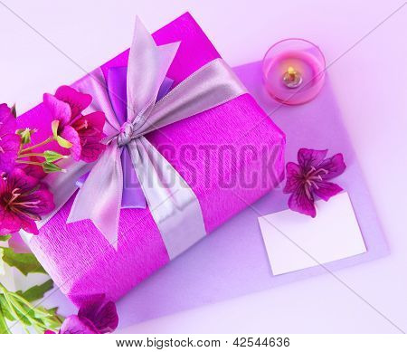 Photo of great pink gift box with silk purple ribbon, beautiful fresh flowers bouquet, romantic candle, blank greeting card, still life isolated on violet background, happy mothers day, love concept