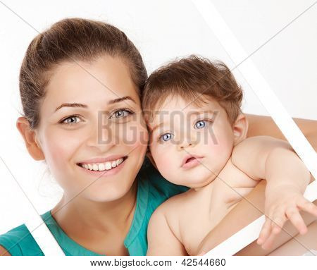 Image of attractive female holding in hands cute baby boy, closeup portrait of young mother hug her little son, white frame decorations, studio shot, happy family, child care and love concept